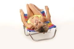 Junge Frau, die im Strandstuhl sich entspannt Stockfotografie