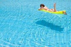 Junge Frau, die im Swimmingpool sich entspannt Stockfoto