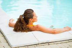 Junge Frau, die im Swimmingpool sich entspannt Hintere Ansicht Stockfoto
