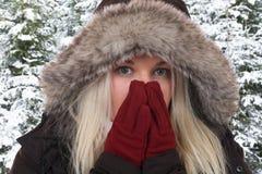 Junge Frau, die im Wald in der Kälte im Winter einfriert Stockfotos