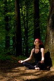 Junge Frau, die im Wald meditiert Lizenzfreies Stockbild