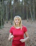 Junge Frau, die im Wald rüttelt Stockfotos