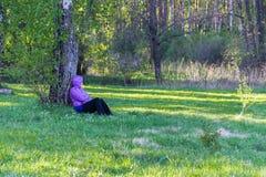 Junge Frau, die im Wald stillsteht Lizenzfreies Stockfoto