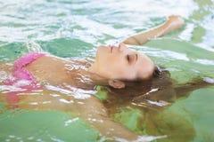 Junge Frau, die im Wasser im Pool sich entspannt Stockfotografie