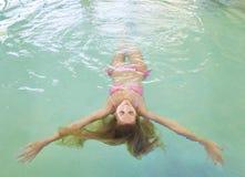 Junge Frau, die im Wasser sich entspannt Lizenzfreie Stockbilder
