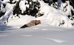 Junge Frau, die im Winterwald schläft Lizenzfreies Stockfoto