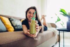 Junge Frau, die im Wohnzimmer und in trinkendem Smoothie sich entspannt Gesunde Di?t lizenzfreies stockbild