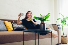 Junge Frau, die im Wohnzimmer und in trinkendem Smoothie sich entspannt Gesunde Di?t lizenzfreie stockbilder