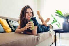 Junge Frau, die im Wohnzimmer und in trinkendem Smoothie sich entspannt Gesunde Di?t stockfotos