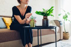 Junge Frau, die im Wohnzimmer und in trinkendem Smoothie sich entspannt H?uslicher Komfort und Gem?tlichkeit lizenzfreies stockfoto