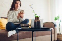 Junge Frau, die im Wohnzimmer unter Verwendung des Smartphone und des trinkenden Kaffees sich entspannt Innendekor stockbilder