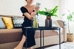 Junge Frau, die im Wohnzimmer unter Verwendung des Smartphone und des trinkenden Smoothie sich entspannt H?uslicher Komfort und G stockbilder