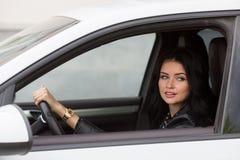 Junge Frau, die innerhalb des Auto-Lächelns sitzt Lizenzfreie Stockfotos