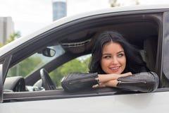 Junge Frau, die innerhalb des Auto-Lächelns sitzt Lizenzfreie Stockbilder