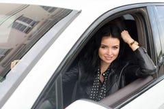 Junge Frau, die innerhalb des Autos lächelt an der Kamera sitzt Stockfoto