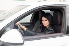 Junge Frau, die innerhalb des Autos lächelt an der Kamera sitzt Lizenzfreie Stockfotos