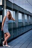Junge Frau, die innerhalb eines modernen Gebäudes aufwirft Stockfoto