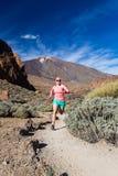 Junge Frau, die in inspirierend Berge der Wüste läuft Stockbilder