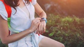 Junge Frau, die intelligente Uhren auf ihrem Handgelenk, während Trekking justiert und entlang Bergwiesen geht lizenzfreies stockbild