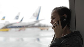 Junge Frau, die am intelligenten Telefon am Flughafen mit Flugzeug auf dem Hintergrund spricht stock video footage