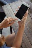 Junge Frau, die intelligentes Telefon auf hölzerner Tabelle hält Stockbild