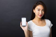 junge Frau, die intelligentes Telefon mit schwarzem Hintergrund zeigt Lizenzfreie Stockfotos