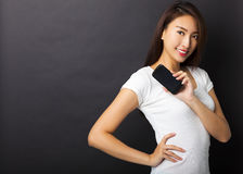 junge Frau, die intelligentes Telefon mit schwarzem Hintergrund zeigt Stockbilder
