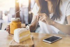 Junge Frau, die intelligentes Telefon verwendet und Kuchen isst lizenzfreies stockfoto