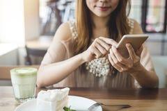 Junge Frau, die intelligentes Telefon verwendet und Kuchen isst lizenzfreies stockbild