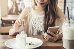 Junge Frau, die intelligentes Telefon verwendet und Kuchen isst lizenzfreie stockfotografie