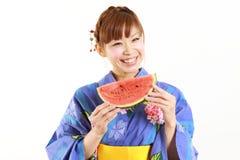 Junge Frau, die japanischen Kimono mit Wassermelone trägt Stockbilder