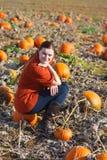 Junge Frau, die an Kürbisfeld arbeitet Lizenzfreie Stockfotos