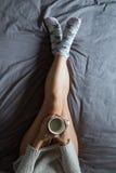Junge Frau, die Kaffee auf Bett trinkt Lizenzfreie Stockbilder