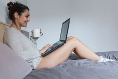 Junge Frau, die Kaffee trinkt und an Laptop arbeitet Stockfotografie