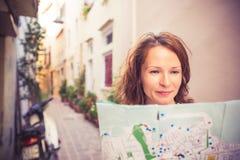 Junge Frau, die Karte schaut Stockbild