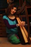 Junge Frau, die keltische Harfe in einem ethno Kostüm spielt Lizenzfreie Stockfotos