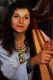 Junge Frau, die keltische Harfe in einem weißen himmlischen historischen Kostüm spielt Lizenzfreie Stockbilder