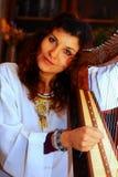 Junge Frau, die keltische Harfe in einem weißen himmlischen historischen Kostüm spielt Lizenzfreies Stockfoto