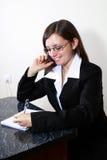 Junge Frau, die Kenntnisse beim Sprechen am Telefon nimmt Lizenzfreies Stockfoto