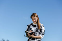 Junge Frau, die Kenntnisse lächelt und nimmt Stockfotos