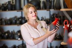 Junge Frau, die Keramik mit rotem Email im Atelier vorwählt Lizenzfreies Stockbild