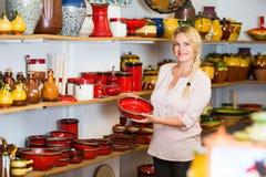 Junge Frau, die Keramik mit rotem Email im Atelier vorwählt Lizenzfreie Stockfotos