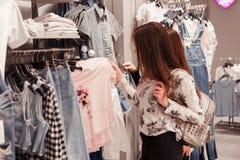 Junge Frau, die Kleidung auf einem Gestell in einem Ausstellungsraum wählt Stockbild