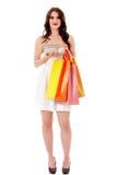 Junge Frau, die kleinen leeren Einkaufskorb und Einkaufstaschen hält Stockfotografie