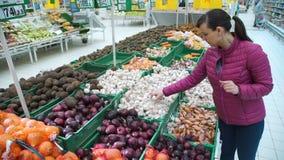 Junge Frau, die Knoblauch am Supermarkt wählt stock footage