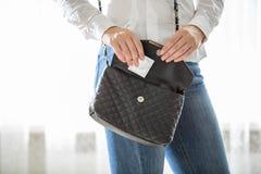 Junge Frau, die Kondom aus Handtasche heraus nimmt Stockbild