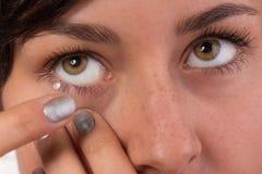 Junge Frau, die Kontaktlinse in ihr Auge einsetzt Stockbilder