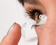 Junge Frau, die Kontaktlinse in ihr Auge einsetzt Lizenzfreie Stockfotografie