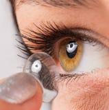 Junge Frau, die Kontaktlinse in ihr Auge einsetzt Stockfoto