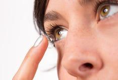 Junge Frau, die Kontaktlinse in ihr Auge einsetzt Stockbild